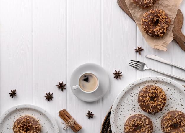 Composição com donuts vitrificados em um prato na mesa de madeira branca.