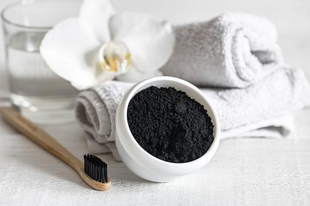 Composição com escova de dente natural de madeira e pó preto para clareamento dentário