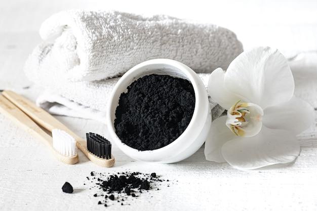 Composição com escovas de dente naturais de madeira, pó clareador de dentes pretos e cópia espaço da flor de orquídea.