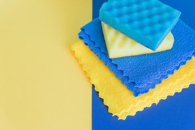 Composição com esponjas de lavar louça e trapos de microfibra sobre fundo azul
