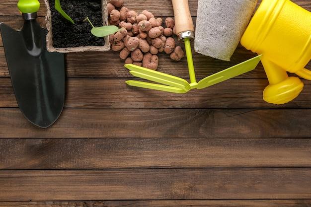 Composição com ferramentas de jardinagem em fundo de madeira
