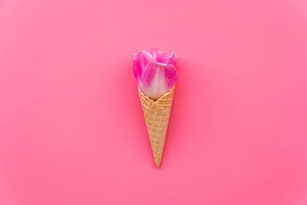 Composição com flor no cone waffle no fundo rosa
