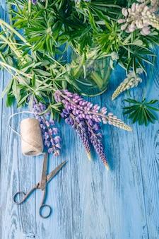 Composição com flores buquê de tremoço azul, velha tesoura rústica