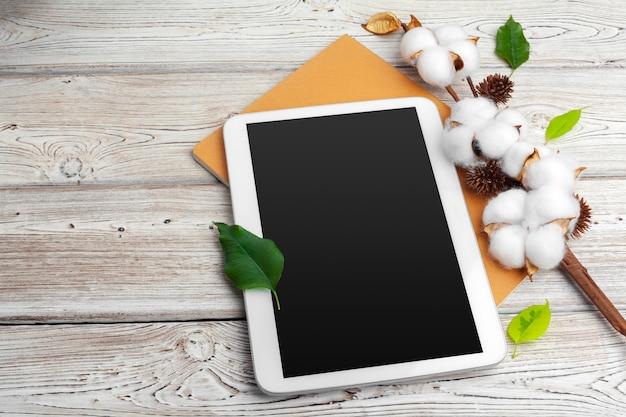 Composição com flores de algodão e tablet digital.