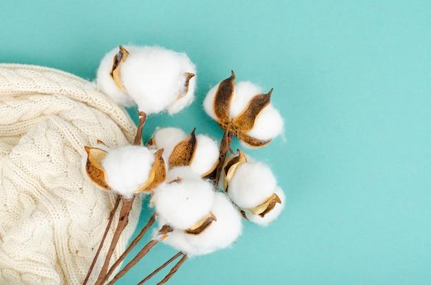Composição com flores de algodão em superfície brilhante