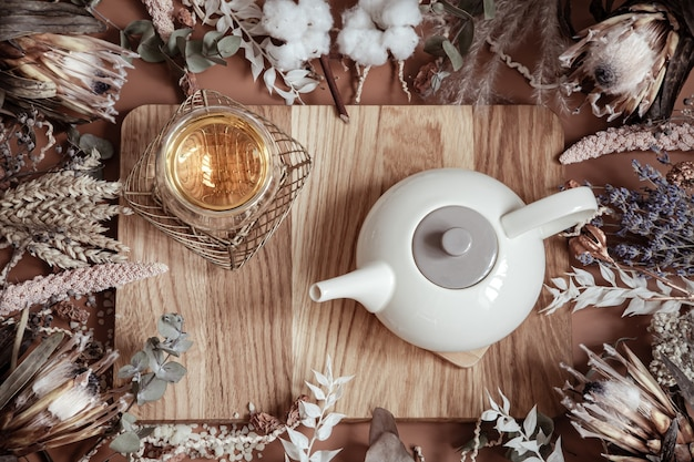 Composição com flores silvestres secas e chá de ervas naturais em um bule sobre uma superfície de madeira.