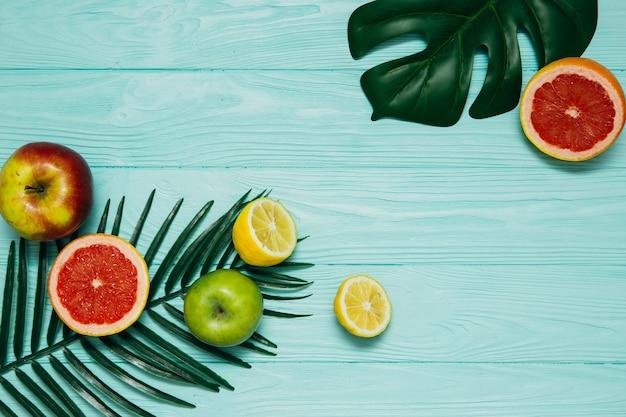 Composição com folhas tropicais e frech frutas no fundo azul