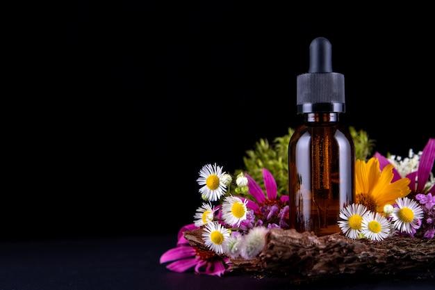 Composição com frasco de vidro no pedestal de casca de árvore com musgo e flores reais