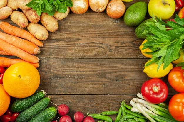 Composição com frutas e vegetais orgânicos frescos variados. pepinos, tomates, rabanete, abacate, ervilhas, batatas, limão, cebola. alimentos na superfície de madeira escura.