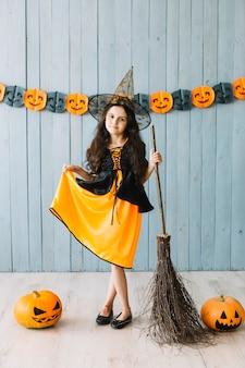 Composição com garota na fantasia de bruxa e abóboras