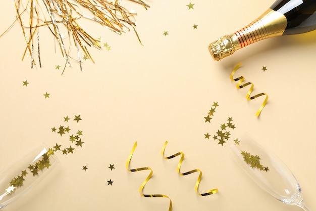 Composição com garrafa de champanhe, óculos e glitter em bege, copie o espaço