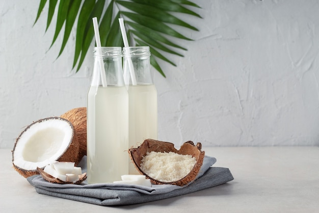 Composição com garrafas de água de coco refrescante na mesa de luz, espaço para texto