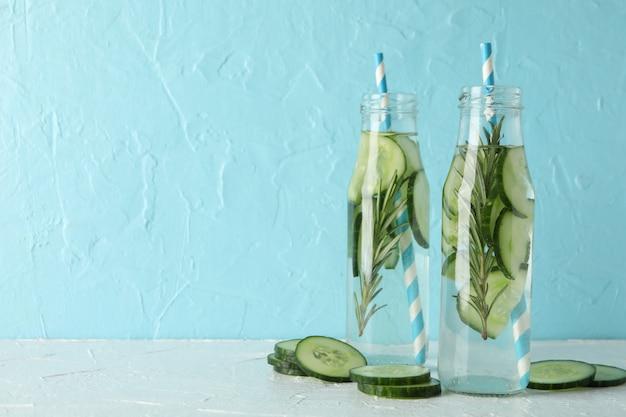 Composição com garrafas de água de pepino contra a superfície azul