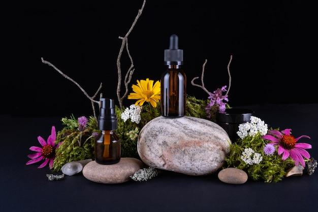Composição com garrafas de vidro em pedestal de pedra com musgos e flores