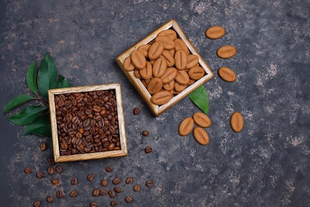 Composição com grãos de café torrados e grãos de café em forma de biscoitos na superfície marrom escura
