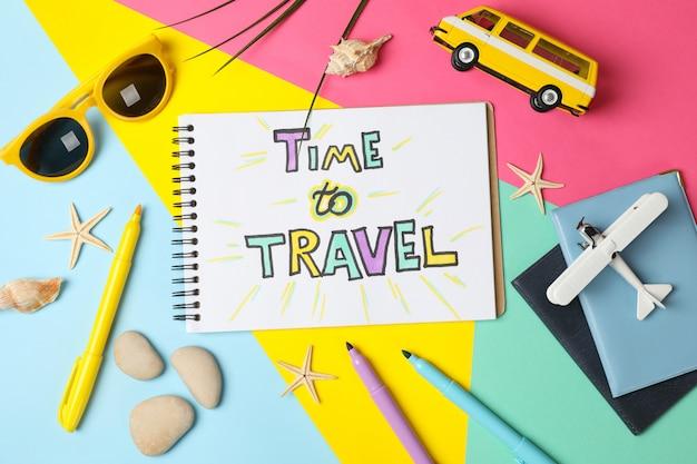 Composição com inscrição hora de viajar no fundo multicolorido