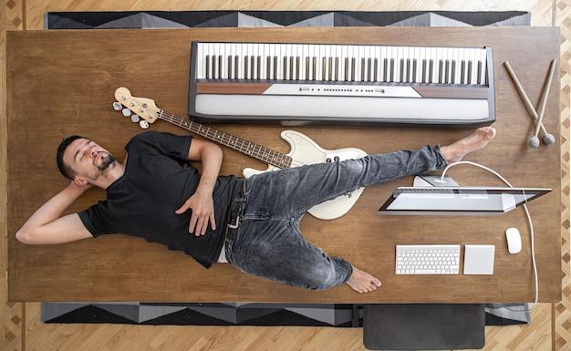 Composição com instrumentos musicais em uma grande mesa de madeira em um estúdio de gravação.