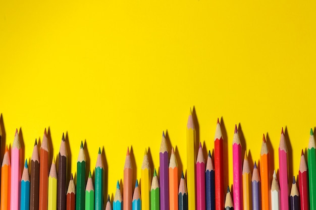 Composição com lápis de cor em um fundo amarelo brilhante. fechar-se. vista do topo. espaço para texto