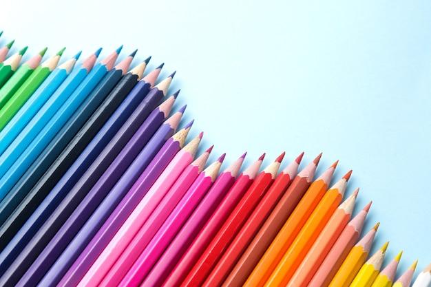 Composição com lápis de cor sobre fundo azul brilhante. vista do topo. espaço para text.frame