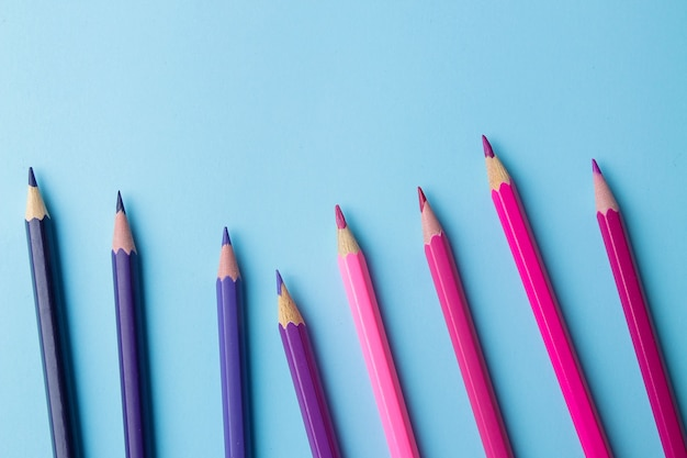 Composição com lápis multicoloridos com lápis sobre um fundo azul brilhante. fechar-se. lugar para texto.