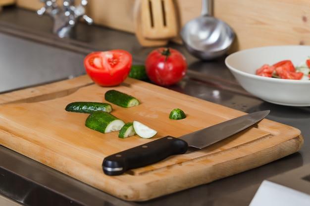 Composição com legumes, pepinos, tomates, faca closeup na cozinha