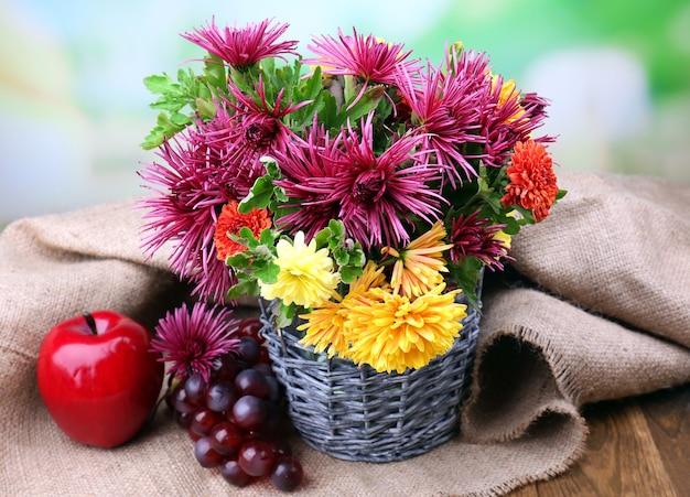 Composição com lindas flores em vaso de vime e frutas, em fundo brilhante