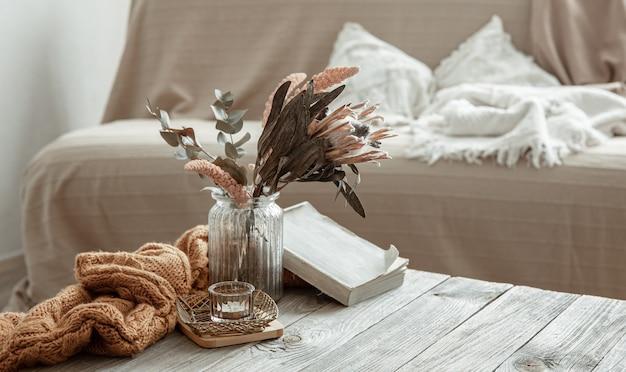 Composição com livro, flor seca e elemento tricotado no interior da sala.