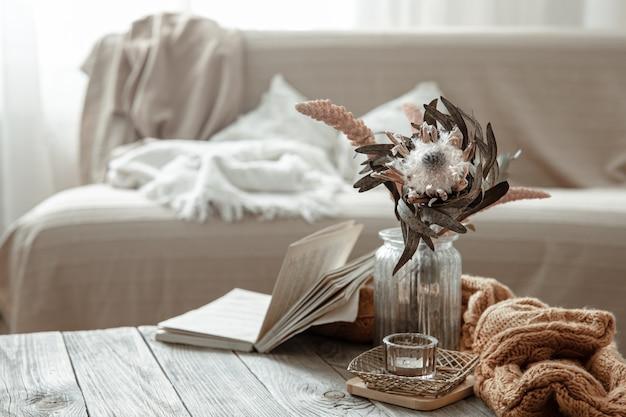Composição com livro, flor seca e elemento tricotado no interior da sala