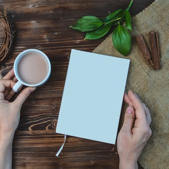 Composição com livro, mão, xícara de café e folhas