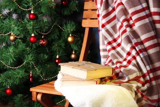Composição com livros e manta na cadeira na árvore de natal