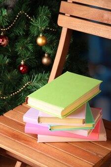 Composição com livros na cadeira no fundo da árvore de natal