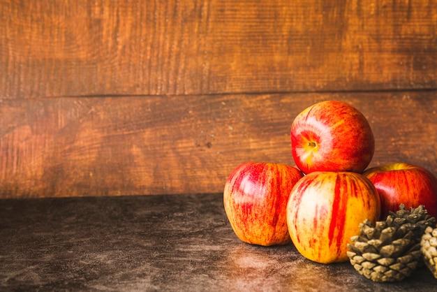 Composição com maçãs vermelhas e pinhas