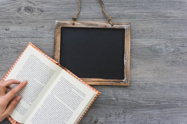 Composição com mão, livro aberto e ardósia em branco