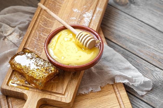 Composição com mel natural e concha de mel em fundo de madeira close-up.
