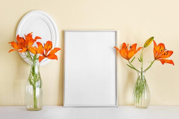 Composição com moldura a4 prata vazia em pé e lírios laranja em vasos de vidro.