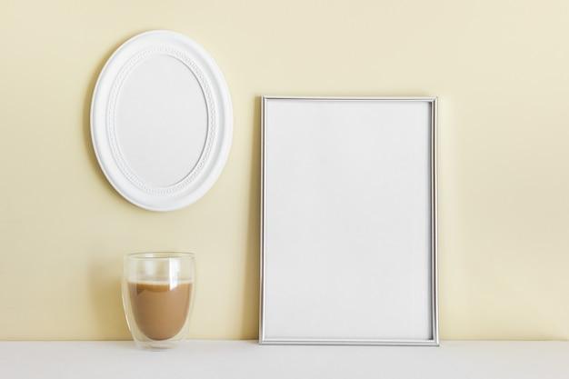 Composição com moldura grande a4 prateada e oval pendurada na parede amarela com café em copo.