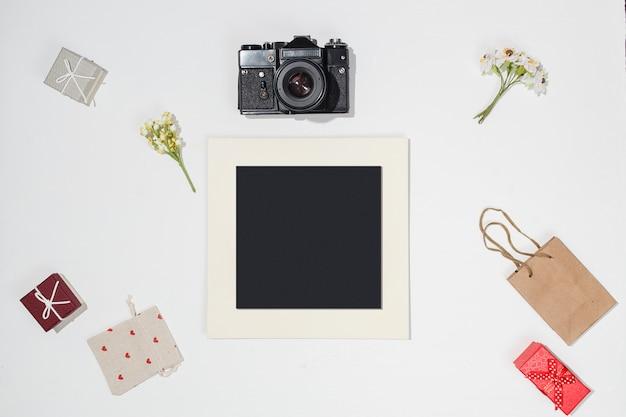 Composição com moldura preta, câmera retro, caixas de presente vermelhas, saco de artesanato, saco de lona com formas de coração vermelho e primavera campo de flores sobre fundo branco. maquete plana leiga na moda