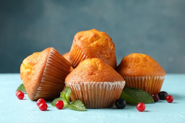 Composição com muffins e frutas sobre fundo azul, close-up