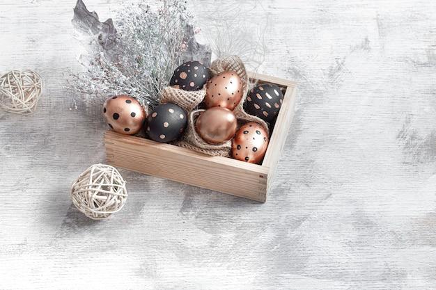 Composição com ovos de páscoa pintados em dourado e preto.