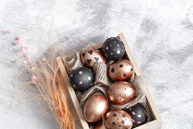Composição com ovos de páscoa pintados em ouro e preto na luz.