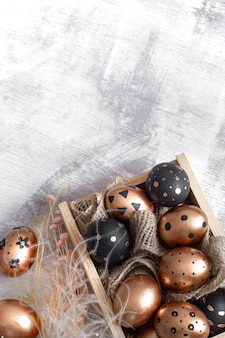 Composição com ovos de páscoa pintados nas cores dourado e preto com enfeites