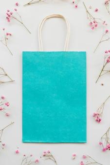 Composição com pacote azul e flores cor de rosa