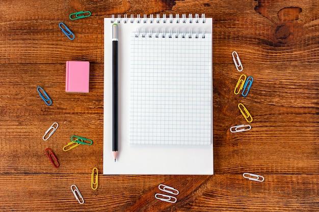 Composição com página colorida de caderno em branco lápis, maquete de marcador e caneta de volta ao conceito de escola
