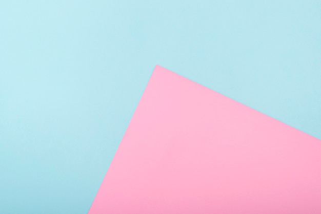 Composição com papel bicolor azul e rosa tom pastel, lay out com espaço para texto