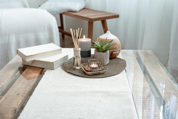 Composição com paus de incenso, difusor, velas e livros na mesa do interior da sala.