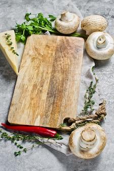 Composição com placa de madeira vazia e legumes na mesa da cozinha conceito de aulas de culinária