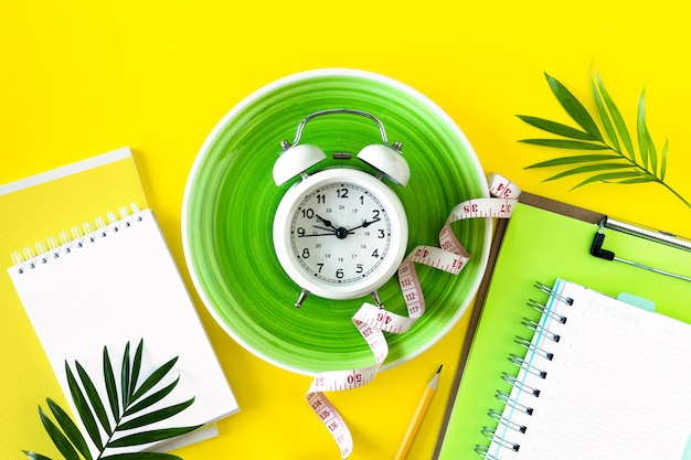 Composição com placa, despertador e fita métrica em um fundo colorido. conceito de dieta e plano de perda de peso, copie o espaço