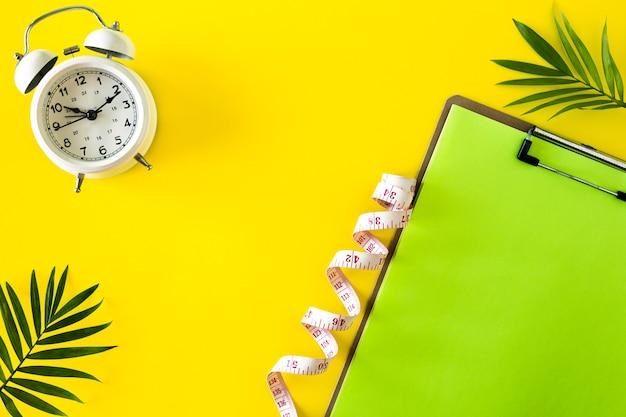 Composição com placa, despertador e fita métrica em um fundo colorido. conceito de dieta e plano de perda de peso, copie o espaço.