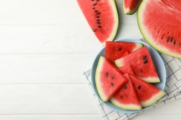 Composição com prato de melancia fresca no espaço de madeira branco, vista superior