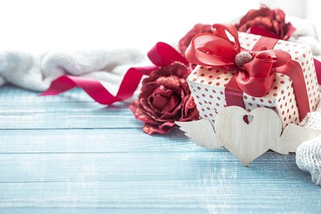 Composição com presente de feriado lindamente embrulhado e elementos decorativos na superfície de madeira close-up.
